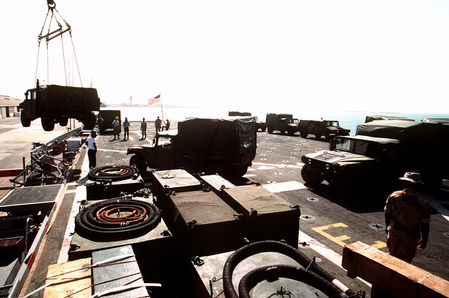 A Marine drives an M998 High-Mobility Multipurpose Wheeled Vehicle (HMMWV) to the edge of the flight deck of the amphibious transport dock USS DUBUQUE (LPD-8) as another HMMWV is unloaded from the ship. The DUBUQUE has brought elements of the 6th Marine Regiment to Saudi Arabia to join Operation Desert Shield