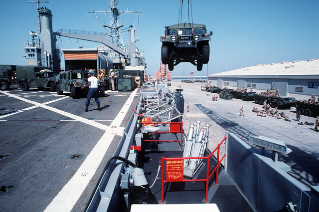 An M-1038 high-mobility multipurpose wheeled vehicle is lifted off of the flight deck of the amphibious transport dock USS DUBUQUE (LPD-8). The DUBUQUE has brought elements of the 6th Marine Regiment to Saudi Arabia to join Operation Desert Shield. One of the DUBUQUE'S four Mark 36 Super Rapid Bloom Off-Board Countermeasures (SRBOC) system launchers is in the foreground