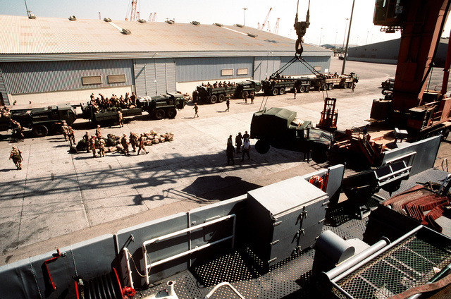 An M-998 high-mobility multipurpose wheeled vehicle is lowered to the pier beside the amphibious transport dock USS DUBUQUE (LPD-8) as Marines climb aboard several logistics vehicle system (LVS) cargo trucks in the background. The DUBUQUE has brought elements of the 6th Marine Regiment to Saudi Arabia to join Operation Desert Shield