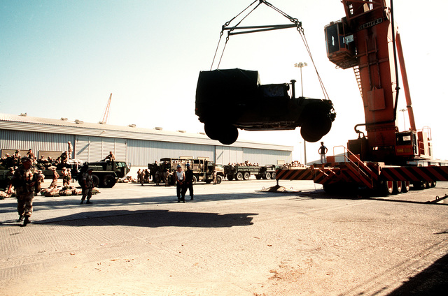 An M-998 high-mobility multipurpose wheeled vehicle is lowered to the pier after being lifted off of the flight deck of the amphibious transport dock USS DUBUQUE (LPD-8). The DUBUQUE has brought elements of the 6th Marine Regiment to Saudi Arabia to join Operation Desert Shield