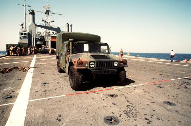 An M998 High-Mobility Multipurpose Wheeled Vehicle (HMMWV) is driven onto the flight deck of the amphibious transport dock USS DUBUQUE (LPD-8) prior to the ship's arrival in Shahran, Saudi Arabia. The DUBUQUE is bringing elements of the 6th Marine Regiment to Saudi Arabia to join Operation Desert Shield