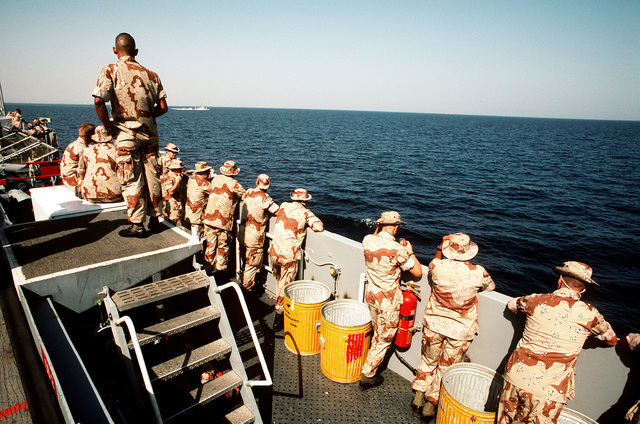 Members of the 6th Marine Regiment watch from aboard the amphibious transport dock USS DUBUQUE (LPD-8) as a Saudi Arabian patrol craft passes off the DUBUQUE's port quarter. The Marines will disembark in Dhahran, Saudi Arabia, to join Operation Desert Shield