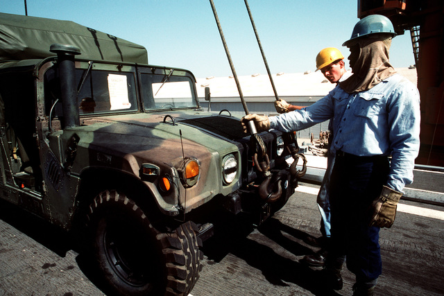 Sailors aboard the amphibious transport dock USS DUBUQUE (LPD-8) hold onto the lifting cables attached to an M-1038 high-mobility multipurpose wheeled vehicle (HHMWV) before the vehicle is lowered to the pier. The DUBUQUE brought elements of the 6th Marine Regiment to Saudi Arabia to join Operation Desert Shield