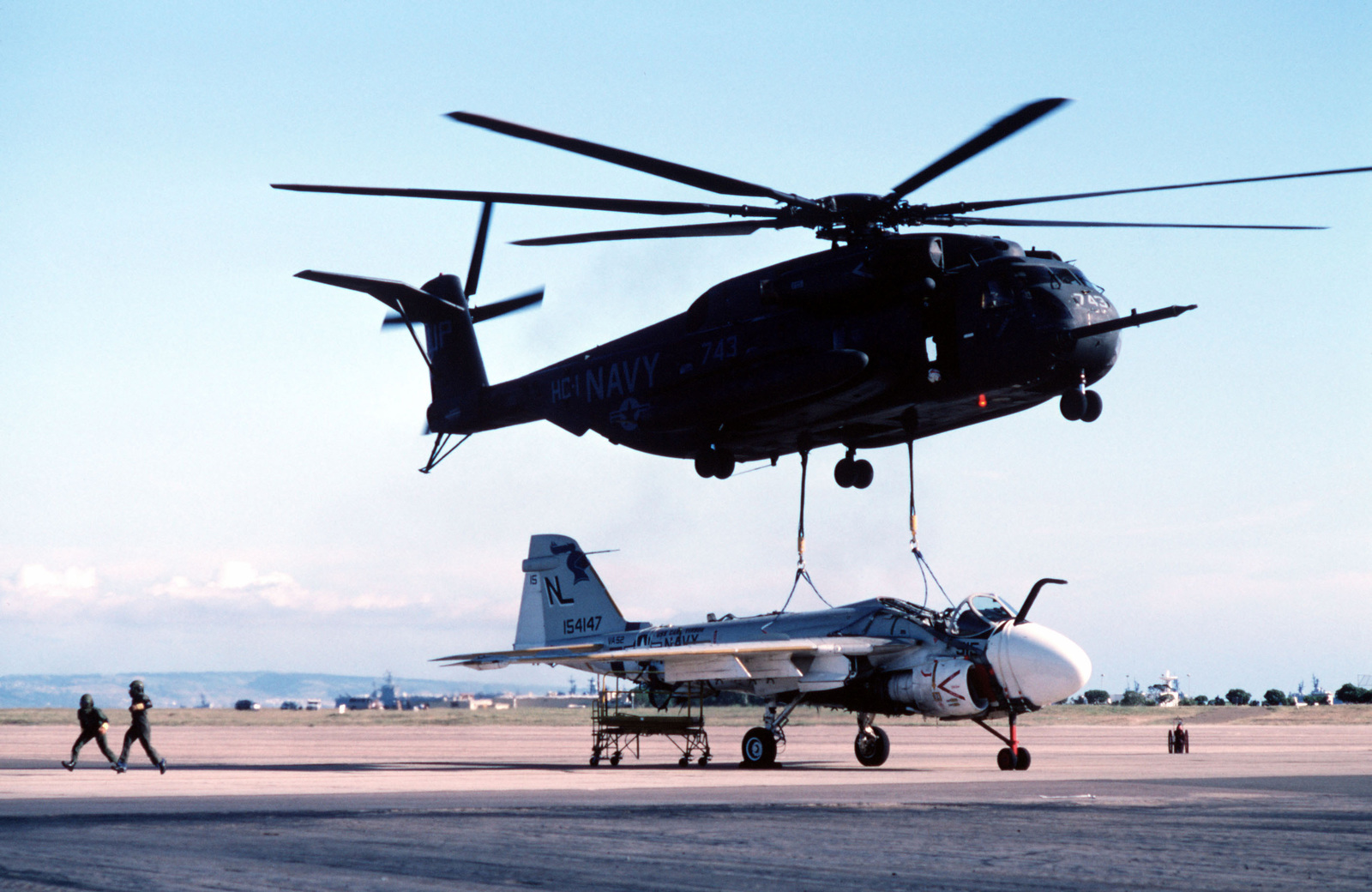A CH-53E Super Stallion helicopter from Helicopter Combat Support Squadron 1 (HC-1) lifts a damaged Attack Squadron 52 (VA-52) A-6E Intruder aircraft. The helicopter will carry the aircraft to the Naval Air Rework Facility, Alameda, California, for repairs. The Intruder was damaged when a hydraulic failure forced it to land with its landing gear retracted
