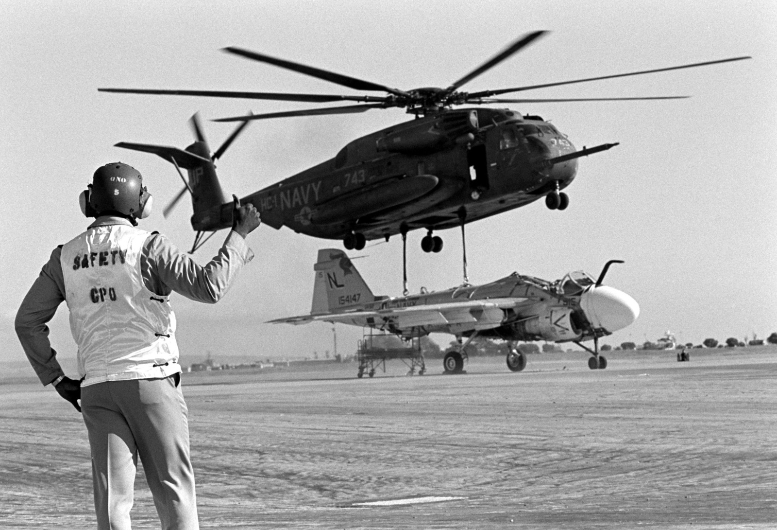 A chief petty officer signals a Helicopter Combat Support Squadron 1 (HC-1) CH-53E Super Stallion helicopter to lift off with a damaged Attack Squadron 52 (VA-52) A-6E Intruder aircraft. The helicopter will carry the aircraft to the Naval Air Rework Facility, Alameda, California, for repairs. The Intruder was damaged when a hydraulic failure forced it to land with its landing gear retracted