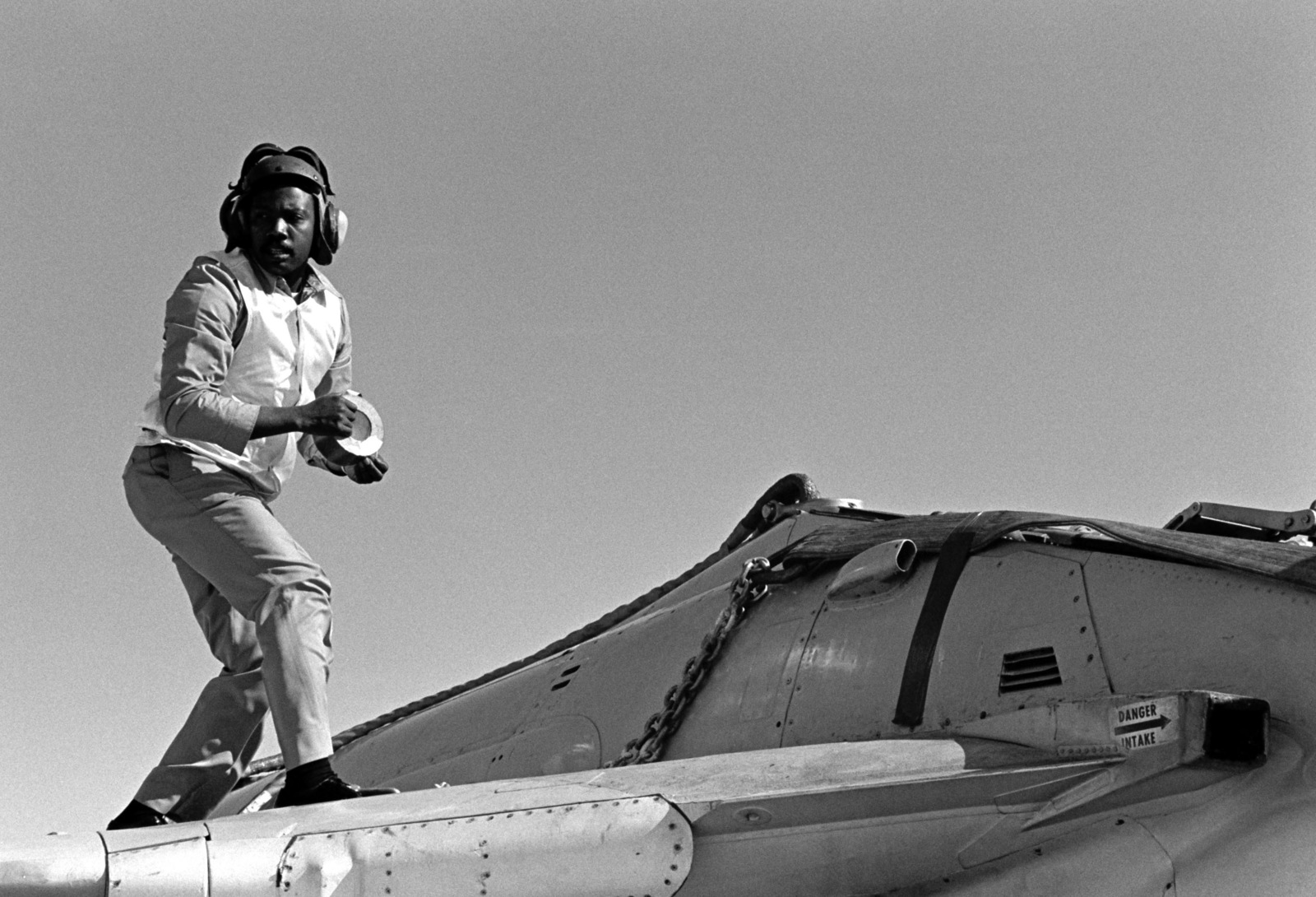 A chief petty officer stands on the wing of a damaged Attack Squadron 52 (VA-52) A-6E Intruder aircraft to tape down sections of a lifting harness. A helicopter will carry the aircraft to the Naval Air Rework Facility, Alameda, California, for repairs. The Intruder was damaged when a hydraulic failure forced it to land with its landing gear retracted