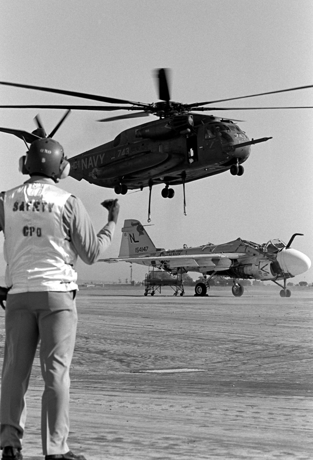 A chief petty officer watches as a Helicopter Combat Support Squadron 1 (HC-1) CH-53E Super Stallion helicopter moves into position over a damaged Attack Squadron 52 (VA-52) A-6E Intruder aircraft. The helicopter will carry the aircraft to the Naval Air Rework Facility, Alameda, California, for repairs. The Intruder was damaged when a hydraulic failure forced it to land with its landing gear retracted