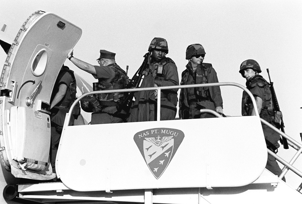Several Seabees from Naval Mobile Construction Battalion 5 (NMCB-5) wait at the top of a staircase while boarding a chartered airliner. One hundred sixty-two members of NMCB-5 are flying to Saudi Arabia to participate in Operation Desert Shield