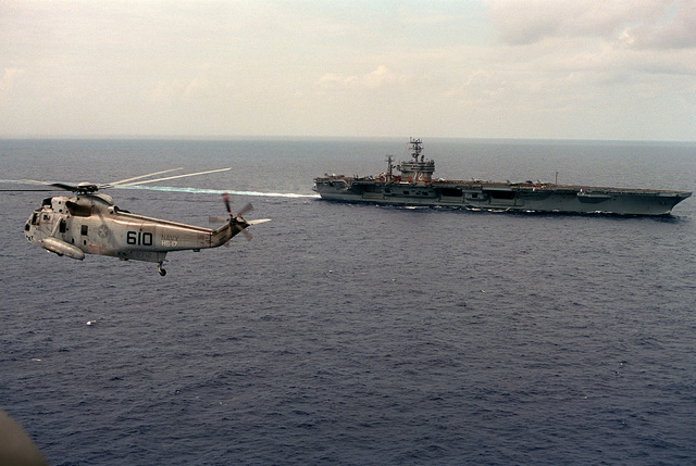 A Helicopter Anti-submarine Squadron 17 (HS-17) SH-3H Sea King helicopter flies near the nuclear-powered aircraft carrier USS ABRAHAM LINCOLN (CVN-72) as the vessel is underway off Cape Henry, Va.