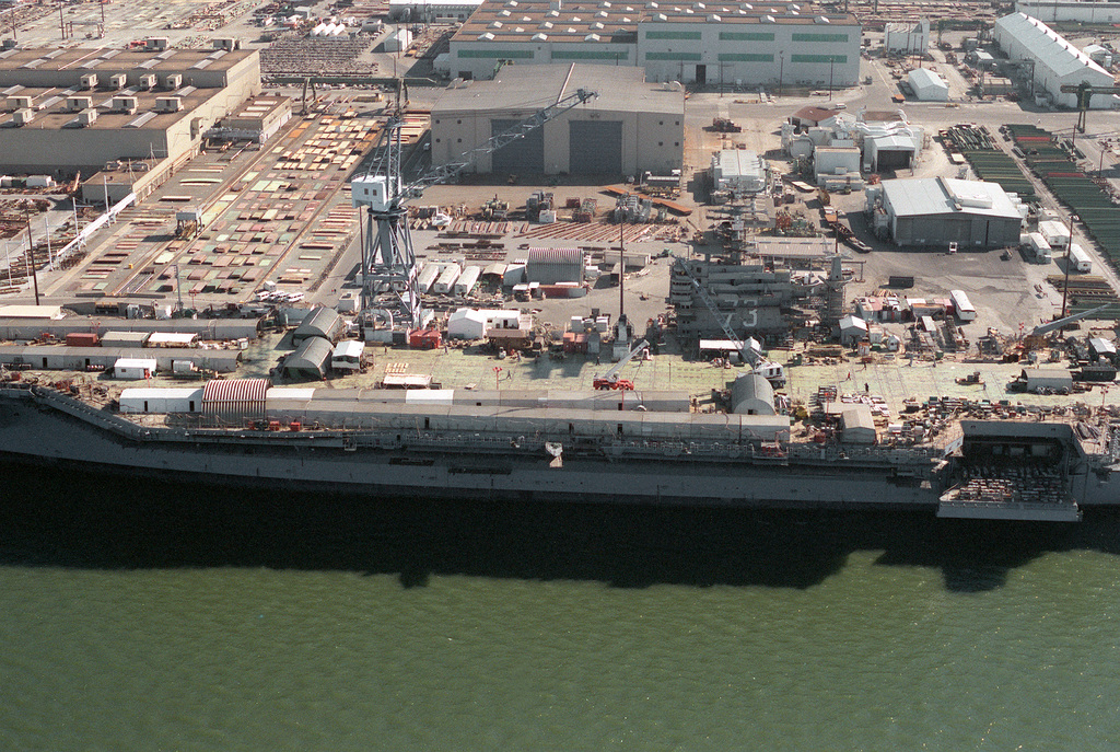 An aerial view of the nuclear-powered aircraft carrier GEORGE WASHINGTON (CVN-73) tied up at the fitting-out pier at the Newport News Shipbuilding and Drydock Co. yard on the James River