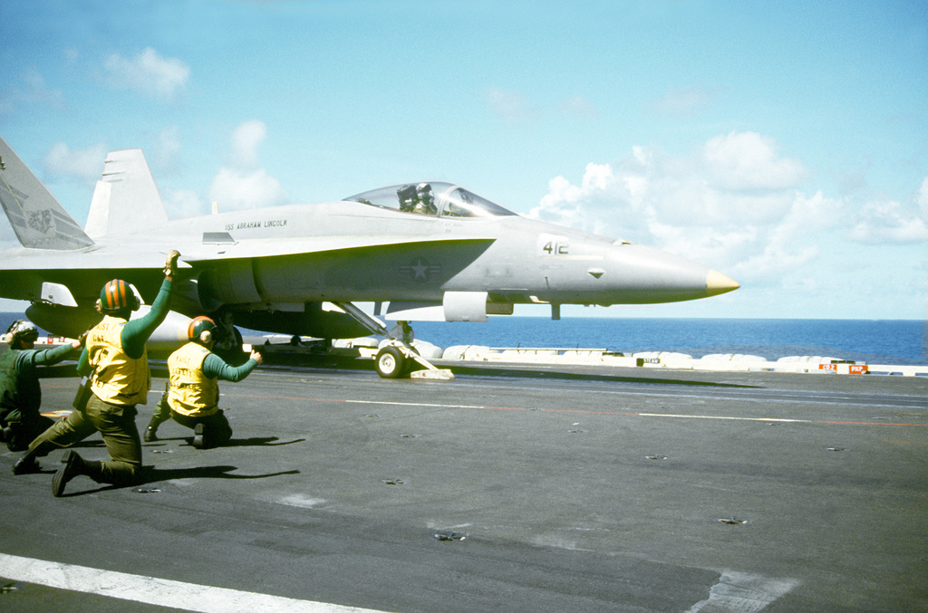 The waist catapult safety observers clear a Strike Fighter Squadron 305 (VFA-305) F/A-18A Hornet aircraft for launch from the No. 4 catapult on the flight deck of the nuclear-powered aircraft carrier USS ABRAHAM LINCOLN (CVN-72)