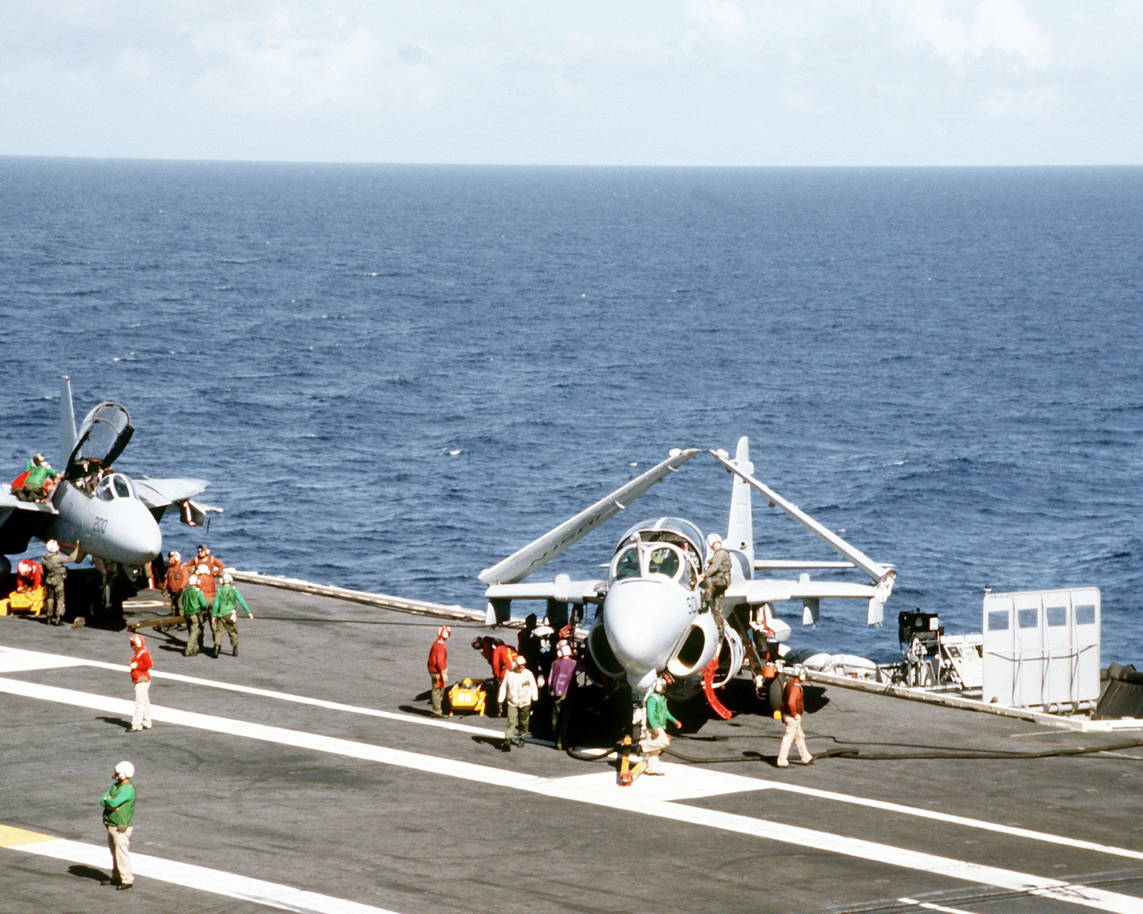 Flight deck crew members and aviation ordnancemen ready an Attack Squadron 96 (VA-96) A-6E Intruder aircraft and a Fighter Squadron 213 (VF-213) F-14A Tomcat aircraft for launch from the flight deck of the nuclear-powered aircraft carrier USS ABRAHAM LINCOLN (CVN-72)