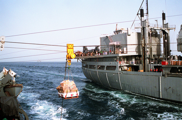 During underway replenishment, a highline rig transfers food stores from the Military Sealift Command combat stores ship USNS SPICA (T-AFS-9), right, to the guided missile destroyer USS GOLDSBOROUGH (DDG-20) during Operation Desert Shield