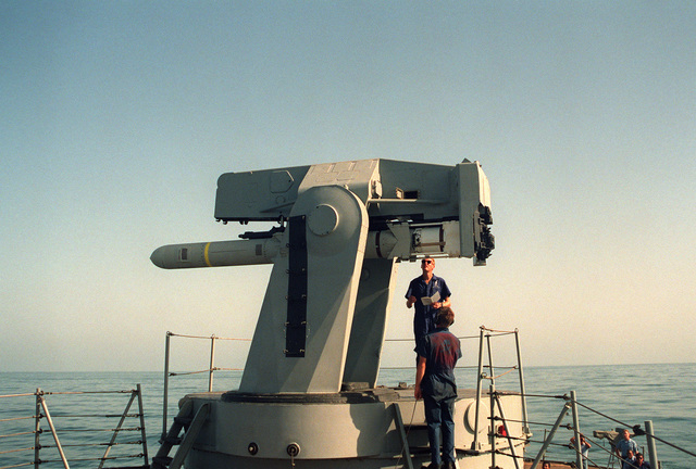 GUNNER's Mate 2nd Class Greenwood and GUNNER's Mate 2nd Class Lawlor inspect an RGM-84A Harpoon missile in a Mark 13 launcher aboard the guided missile destroyer USS GOLDSBOROUGH (DDG 20) duirng Operation DESERT SHIELD