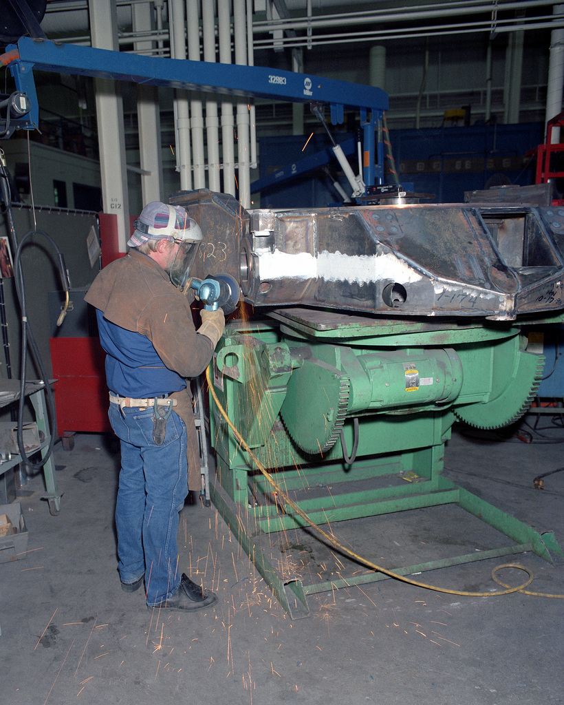 John Bloomfield, a civilian employee, grinds down a weld on an M-39 bottom carriage for an M-198 155mm howitzer