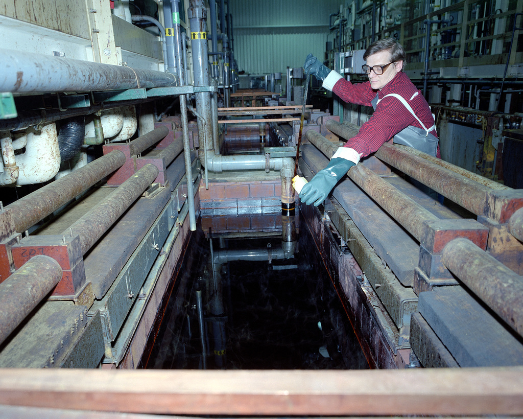 Joseph Rock, a civilian employee, takes a sample of chrome solution from a holding tank in Building 212W