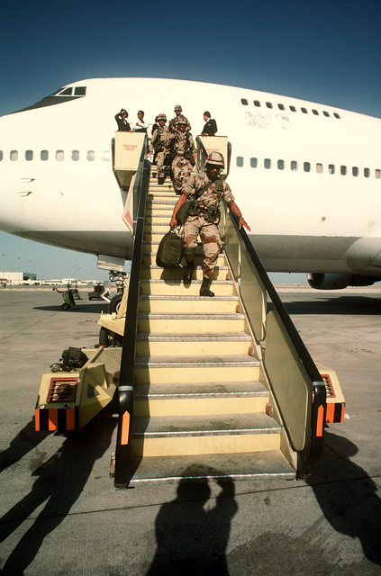 Troops disembark from a Civil Reserve Air Fleet (CRAF) Boeing 747 aircraft after arriving in the region in support of Operation Desert Shield