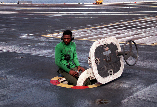 Aviation Boatswain's Mate 3rd Class Herman Miranda monitors the control panel for a Mark 7 jet blast deflector which is being tested on the flight deck of the nuclear-powered aircraft carrier USS ABRAHAM LINCOLN (CVN-72)