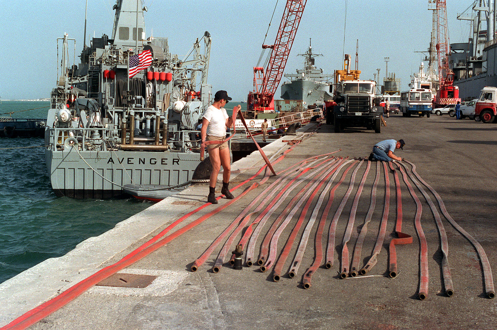 The mine countermeasures ship USS AVENGER is moored to the pier as crew members inspect fire hoses nearby. The AVENGER and other vessels have been delivered to the region aboard the Dutch heavy lift ship SUPER SERVANT 3 in support of Operation Desert Shield