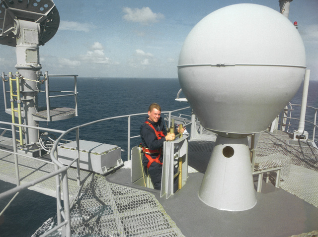 A crew member stands beside a radar dome aboard the nuclear-powered aircraft carrier USS ABRAHAM LINCOLN (CVN-72) as the vessel is underway during its circumnavigation of South America