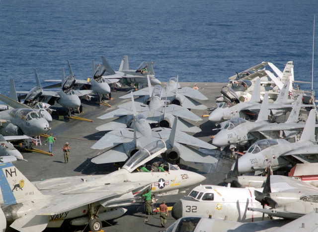 A Fighter Squadron 213 (VF-213) F-14A Tomcat aircraft is serviced on the crowded flight deck of the nuclear-powered aircraft carrier USS ABRAHAM LINCOLN (CVN-72) as the vessel is underway on its circumnavigation of South America