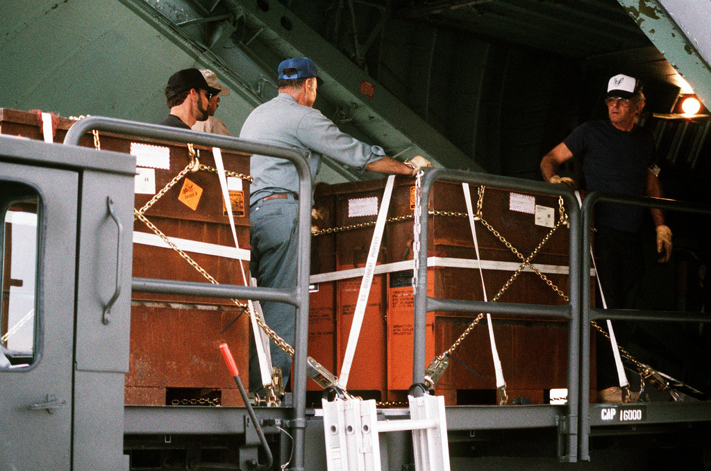 Edward Mitchell, Jim Jones and Bill Benkovich, all ammunition operations personnel, load a C-141B Starlifter aircraft with containers of 30mm high explosive incendiary (HEI) ammunition bound for the Persian Gulf area during Operation Desert Shield