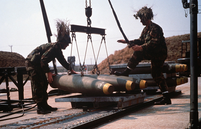 SENIOR AIRMAN Phillip Ruddock, left, and AIRMAN 1ST Class Thomas Hearl of the 6151st Consolidated Aircraft Maintenance Squadron (6151st CAMS) lower three Mark 82 500-pound bombs onto a pallet during the joint South Korean/United States exercise TEAM SPIRIT '89