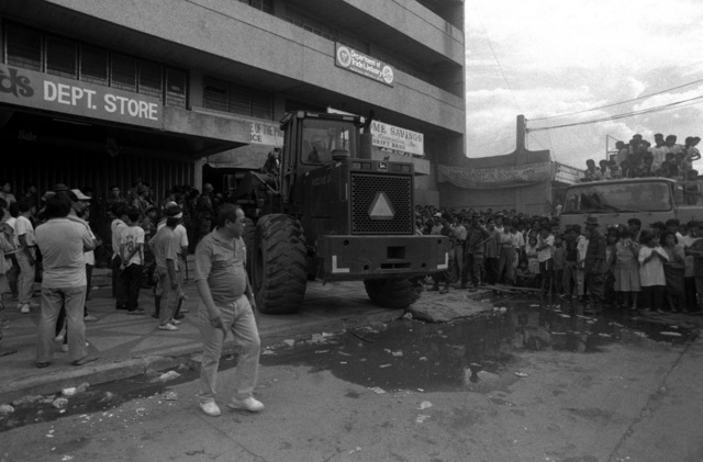 Onlookers watch rescue workers maneuver equipment as they prepare to conduct rescue and relief efforts in an area which sustained earthquake damage