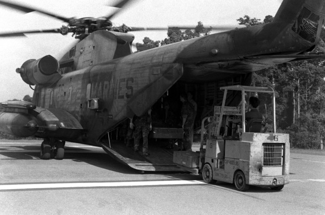 United States Marine unload supplies from a CH-53D Sea Stallion helicopter during rescue and recovery efforts in an area which sustained earthquake damage