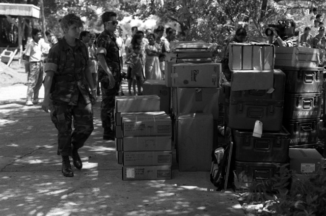 United States Marines stand by boxes of supplies brought in to aid victims during rescue and recovery efforts in an area which sustained earthquake damage