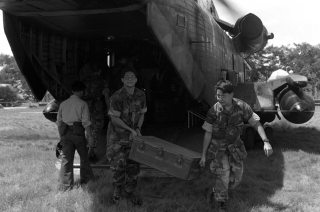 United States Marines unload supplies from a CH-53D Sea Stallion helicopter during rescue and recovery efforts in an area which sustained earthquake damage
