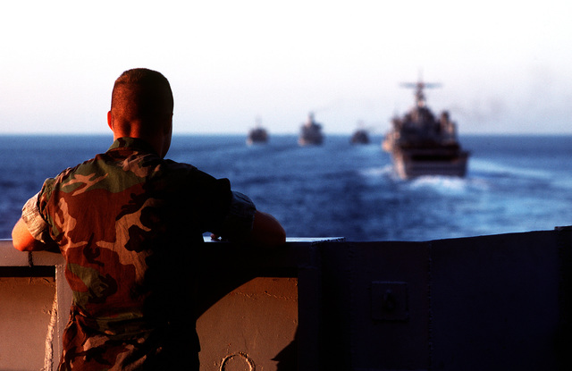 A Marine aboard the amphibious transport dock USS RALEIGH (LPD-1) watches other ships of the amphibious task force steaming ahead of the RALEIGH. The ships and their embarked Marines are at sea in support of Operation Desert Shield