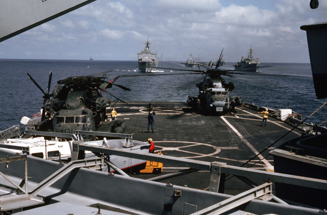 A Marine Heavy Helicopter Squadron 464 (HMH-464) CH-53E Super Stallion helicopter idles on the flight deck of the amphibious transport dock USS RALEIGH (LPD 1) as other ships of the amphibious task force steam in formation behind. The ships and their embarked Marines are at sea in support of Operation DESERT SHIELD