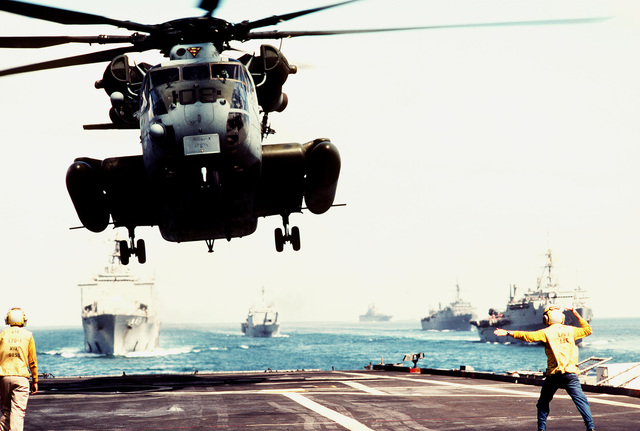A Marine Heavy Helicopter Squadron 464 (HMH-464) CH-53E Super Stallion helicopter comes in to land on the flight deck of the amphibious transport dock USS RALEIGH (LPD-1) as other ships of the amphibious task force steam in formation behind. The ships and their embarked Marines are at sea in support of Operation Desert Shield