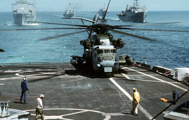 A Marine Heavy Helicopter Squadron 464 (HMH-464) CH-53E Super Stallion helicopter lands on the flight deck of the amphibious transport dock USS RALEIGH (LPD-1) as other ships of the amphibious task force steam in formation behind. The ships and their embarked Marines are at sea in support of Operation Desert Shield