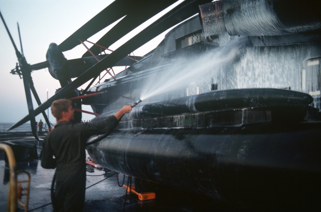 A Marine rinses soap off the side of a Marine Heavy Helicopter Squadron 464 (HMH 464) CH-53E Super Stallion helicopter on the flight deck of the amphibious transport dock USS RALEIGH (LPD 1). The RALEIGH is part of an amphibious task force supporting Operation DESERT SHIELD