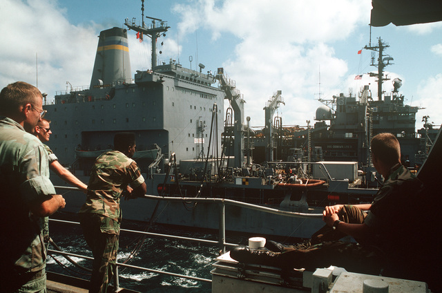 Four Marines aboard the amphibious transport dock USS RALEIGH (LPD 1) watch as their ship and the amphibious assault ship USS OKINAWA (LPH 3), background, conduct underway replenishment operations with the fleet oiler USNS ANDREW J. HIGGINS (T-AO-190). The ships are part of an amphibious task force supporting Operation DESERT SHIELD