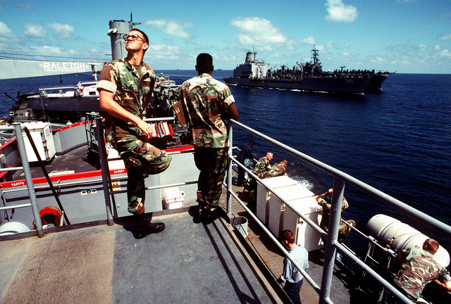 Marines and sailors aboard the amphibious transport dock USS RALEIGH (LPD-1) watch as the fleet oiler USNS ANDREW J. HIGGINS (T-AO-190) and the amphibious assault ship USS OKINAWA (LPH-3) conduct an underway replenishment. The ships are part of an amphibious task force support Operation Desert Shield
