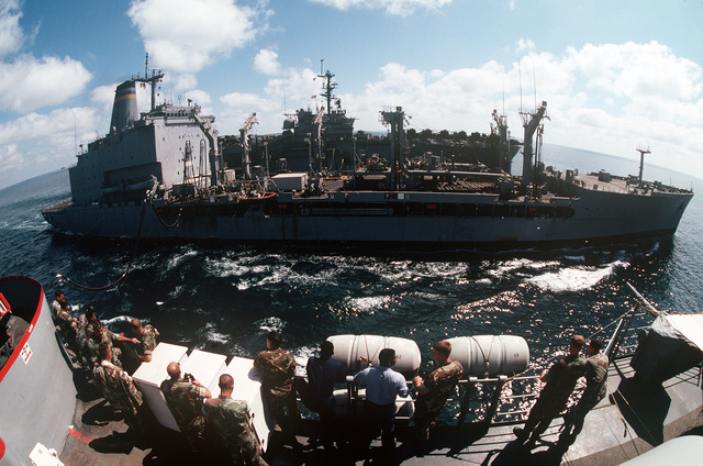 Marines and sailors aboard the amphibious transport dock USS RALEIGH (LPD 1) watch as their ship and the amphibious assault ship USS OKINAWA (LPH 3), background, conduct underway replenishment operations with the fleet oiler USNS ANDREW J. HIGGINS (T-AO-190). The ships are part of an amphibious task force supporting Operation DESERT SHIELD