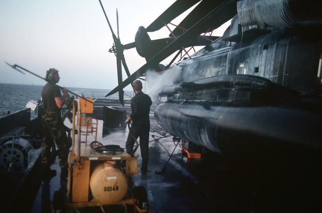 Two Marines complete a fresh-water washdown of a Marine Heavy Helicopter Squadron 464 (HMH 464) CH-53E Super Stallion helicopter on the flight deck of the amphibious transport dock USS RALEIGH (LPD 1). The RALEIGH is part of an amphibious task force supporting Operation DESERT SHIELD