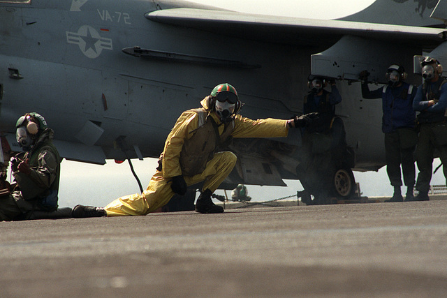 Wearing an MCU-2P protective mask as part of a Nuclear-Biological-Chemical (NBC) warfare drill, LT. Thomas Stubblefield signals to the deck edge operator during the launch of an A-7E Corsair aircraft on the flight deck of the aircraft carrier USS JOHN F. KENNEDY (CV-67). The KENNEDY is operating in support of Operation Desert Shield