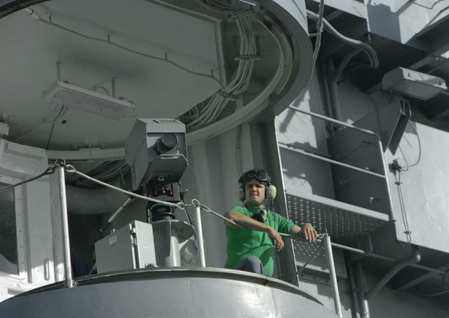 A crew member stands at the railing beside a Pilot Landing and Take-Off System (PLATS) camera aboard the nuclear-powered aircraft carrier USS ABRAHAM LINCOLN (CVN-72). The vessel is underway during its circumnavigation of South America