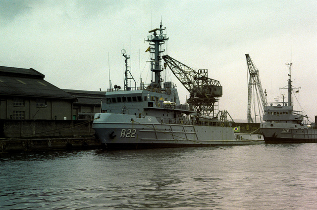 A port bow view of the Brazilian fleet ocean tug TRIDENTE (R-22) tied up at the south wall of the naval base, with the Brazilian training ship &-16 tied up behind it