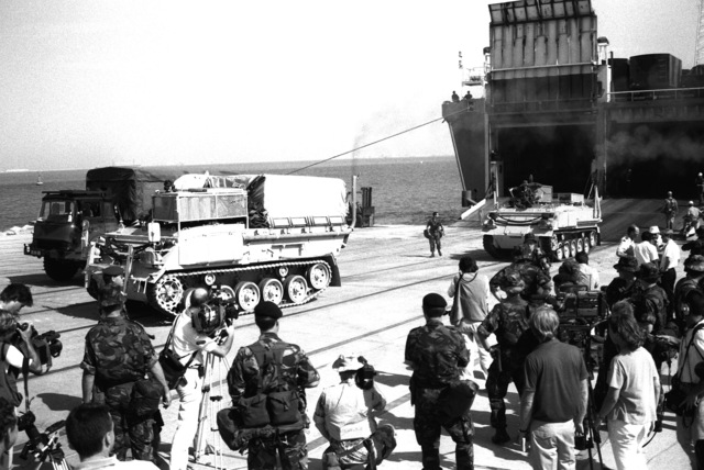 As members of the news media look on, two FV432 armored vehicles assigned to the British army's 7th Armour Brigade are driven onto the pier from the stern ramp of the Danish cargo ship Dana Cimbria after its arrival at the King Abdul Aziz Naval Port during Operation Desert Shield.