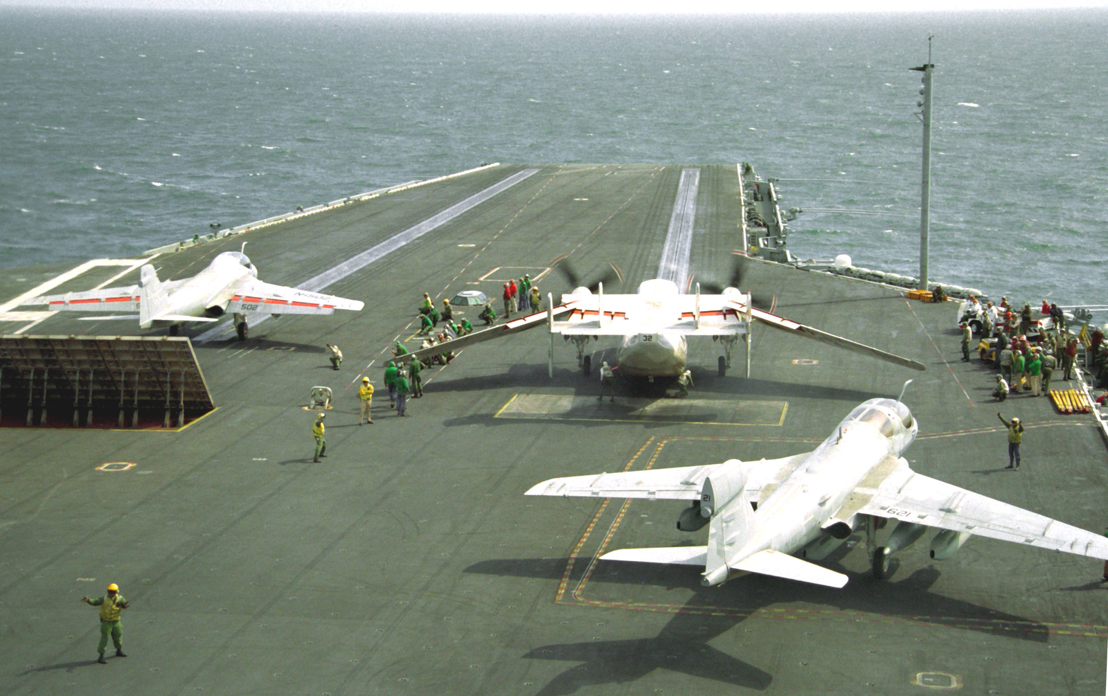 An Attack Squadron 95 (VA-95) A-6E Intruder aircraft, left, and a Fleet Logistic Support Squadron 30 (VRC-30) C-2A Greyhound aircraft, center, are readied for launch on the bow catapults aboard the nuclear-powered aircraft carrier USS ABRAHAM LINCOLN (CVN-72). A Tactical Electronic Warfare Squadron 135 (VAQ-135) EA-6B Prowler aircraft, right, waits to taxi into launch position. The LINCOLN is underway off the coast of Argentina