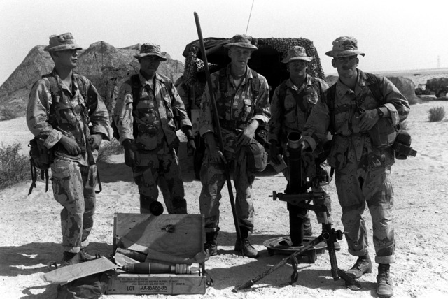 Members of a mortar crew from Weapons Co., 1ST Bn., 7th Marines, gather for a photograph behind their M-252 81mm mortar during Operation Desert Shield.