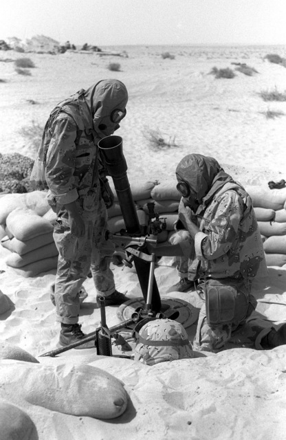 Wearing their M-17A1 field protective masks, two Marines from Weapons Co., 1ST Bn., 7th Marines, conduct gun drills with an M-252 81mm mortar during Operation Desert Shield.