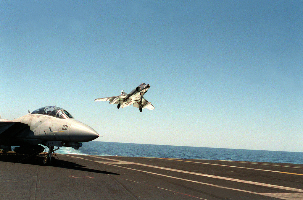 An Argentine navy Super Etendard aircraft approaches the flight deck of the nuclear-powered aircraft carrier USS ABRAHAM LINCOLN (CVN-72). The aircraft is taking part in touch-and-go operations aboard the LINCOLN during the ship's circumnavigation of South America. A Fighter Squadron 114 (VF-114) F-14 A aircraft is in the foreground