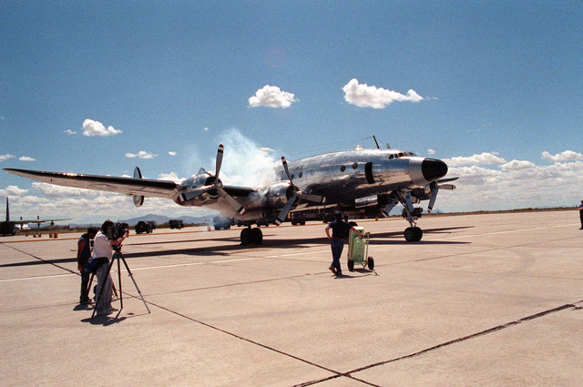 A cameraman films Columbine II, the presidential aircraft for former President Dwight D. Eisenhower, as the plane starts its engines in preparation for departure. After undergoing restoration at the Aerospace Maintenance and Regeneration Center following over 20 years in storage, the C-121A aircraft is leaving the base to undergo further repair work at a private company