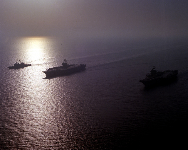 An aerial view of, from left, the guided missile cruiser USS SAN JACINTO (CG-56), the aircraft carriers USS JOHN F. KENNEDY (CVB-67), and USS SARATOGA (CV-60) and the guided missile cruiser USS BIDDLE (CG-34) underway. After 45 days on station in support of Operation Desert Shield, the KENNEDY and its battle group are being relieved by the SARATOGA and its battle group